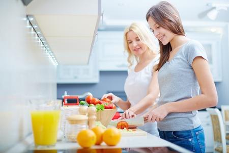 10 代の少女と彼女の母は台所で料理の背景上の肖像画 写真素材