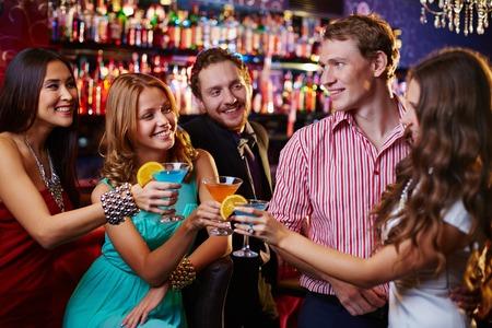 Groep vrienden roosteren met cocktails in de bar