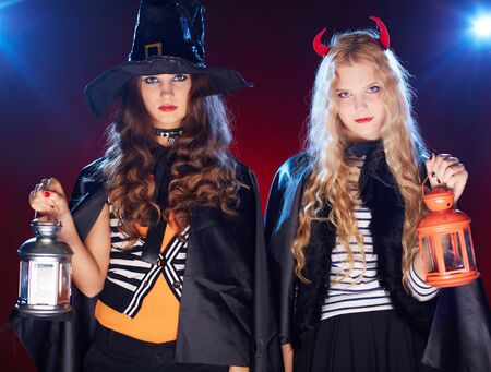 antichrist: Portrait of two Halloween girls with lanterns looking at camera