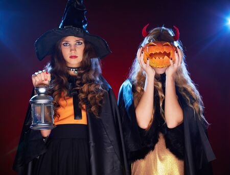 Portrait of two females with lantern and pumpkin posing for camera photo