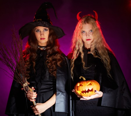 haunt: Portrait of two sullen females with broom and pumpkin looking at camera