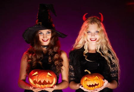 Portrait of two happy females with pumpkins looking at camera with smiles photo