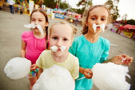 algodon de azucar: Imagen de chicas divertidas con algodón de azúcar que presenta en el parque infantil al aire libre