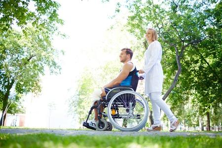 persona en silla de ruedas: Enfermera bonita caminando con paciente de sexo masculino en una silla de ruedas en el parque