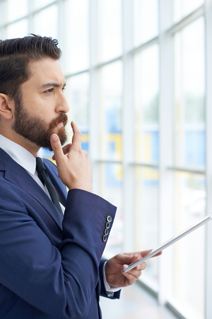 elegant business man: Image of young businessman with touchpad looking through the window in office Stock Photo