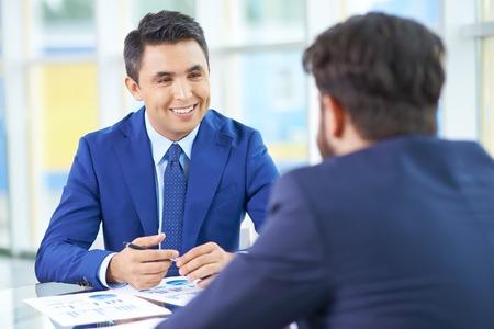 Afbeelding van knappe zakenman in pak communiceren met zijn collega op de vergadering van