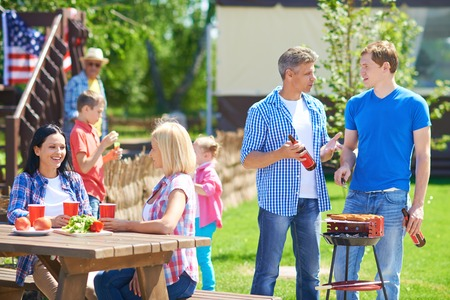 Portrait of young men frying sausages and talking in the countryside at weekend with their families near by photo