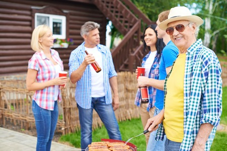 dacha: Portrait of happy senior man frying sausages and looking at in the countryside at weekend with group of young friends talking on background Stock Photo