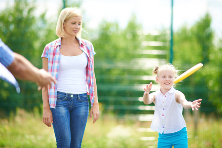 flying disc: Little girl playing with flying disc in the countryside with her mother near by Stock Photo