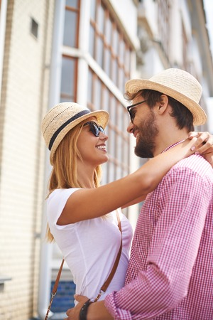 committed: Happy girl and her boyfriend in hats and sunglasses looking at one another with smiles outdoors