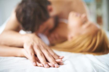 mujer en la cama: Manos de mujer y hombre acostado en la cama
