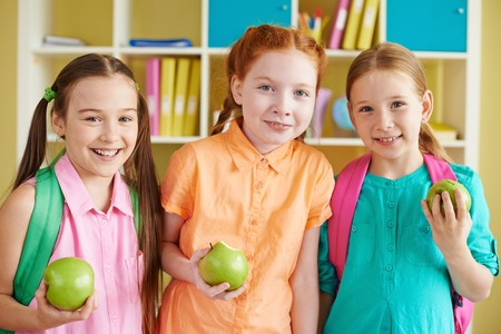 Portrait of charming girls with backpacks and green apples looking at camera photo