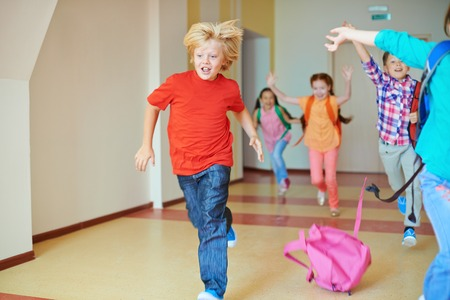 Portrait of happy classmates with backpacks running down the corridor after lesson photo