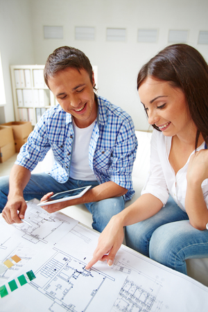 Portrait of young couple discussing plan of new flat