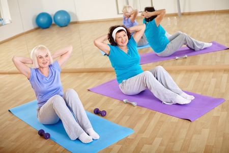 Backs of sporty females doing physical exercise for belly