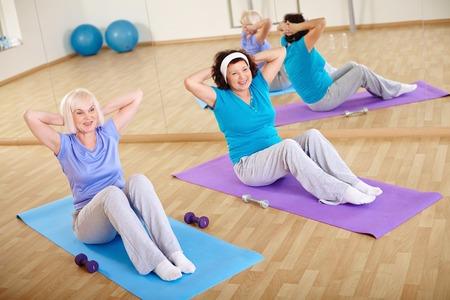 senior fitness: Backs of sporty females doing physical exercise for belly