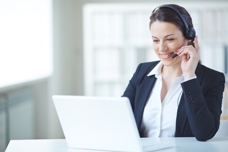 Young customer support representative consulting client on-line