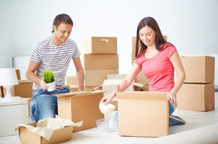 settler: Happy young couple sitting on the floor of new flat and unpacking boxes