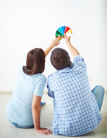 Rear view of young couple sitting on the floor of new house and looking at colorful palette Stock Photo