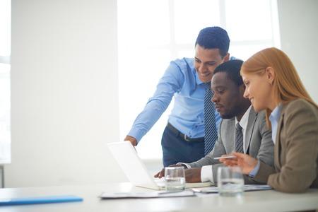 Gruppo di soci d'affari fiducioso lavorando con il portatile in ufficio