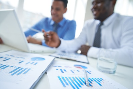 financial education: Business documents, glass of water and pen with two businessmen on background Stock Photo