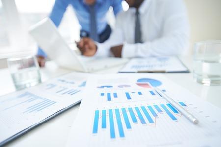 Documenten met grafiek en de grafiek en pen op de achtergrond van twee medewerkers