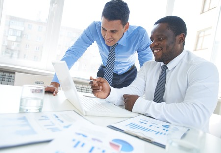 project: African-american businessman pointing at laptop screen while explaining project to his colleague