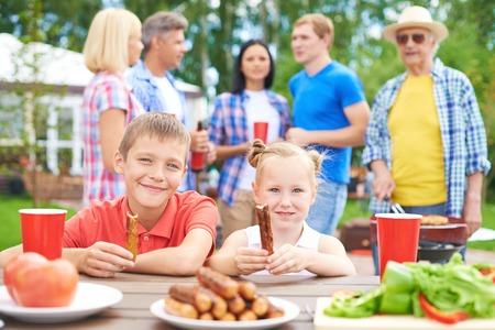 ni�os comiendo: Ni�os comiendo salchichas durante su reuni�n familiar