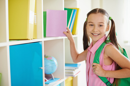 elementary students: Girl taking book Stock Photo