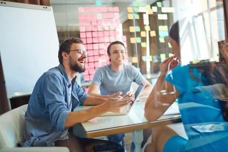 trabajando: Socios de negocios jovenes que comparten ideas y la planificaci�n del trabajo en la reuni�n en la oficina Foto de archivo