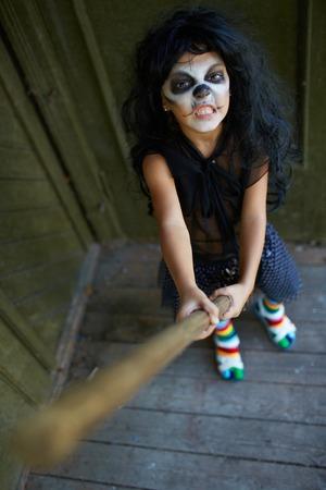 bared teeth: Portrait of eerie girl with broom