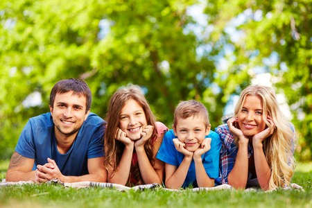 Happy family of four relaxing on grass in park photo
