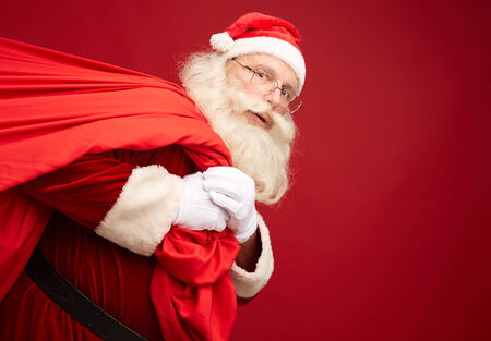 Portrait of Santa Claus with huge red sack in isolation photo