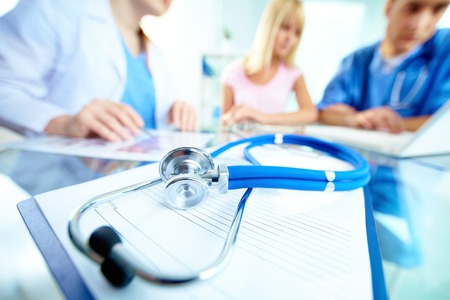 Stethoscope and document on background of doctors and patient working with laptop photo