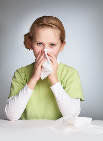 Portrait of an ill girl blowing her nose photo