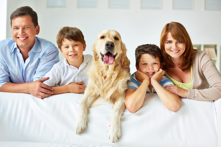 family on couch: Smiling family of four with a dog