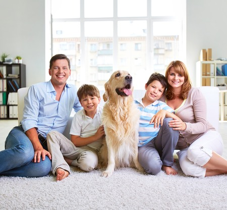 Family of four sitting on carpet Stock Photo