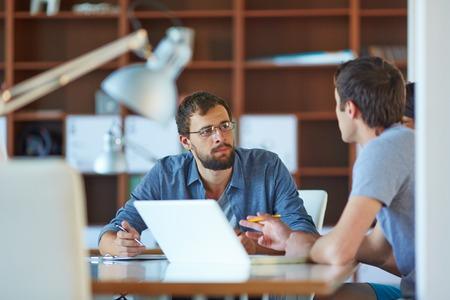 ležérní: Dva podnikatelé interakce na setkání v kanceláři Reklamní fotografie