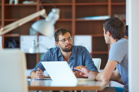 serious: Two businessmen interacting at meeting in office Stock Photo