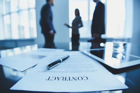 foreground focus: Close-up of contract on office table
