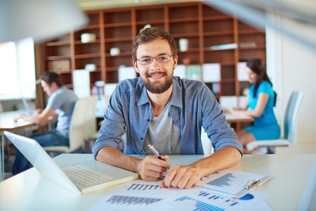 calm woman: Handsome businessman in casual looking at camera in office on background of his partners Stock Photo