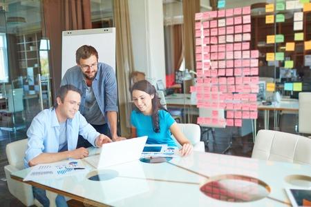 puesto de trabajo: Grupo de socios de negocios en la escucha ocasional a hombre joven apuntando a la pantalla del port�til en la oficina