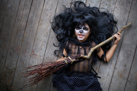antichrist: Grinning girl in black wig holding broom and looking at camera Stock Photo