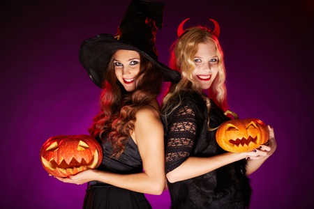 Portrait of two happy females with carved Halloween pumpkins photo