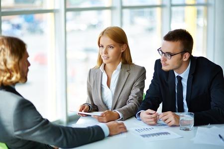 Zwei ernste Geschäftspartner aufmerksam zuhören, um junge Menschen auf der Sitzung im Büro Standard-Bild - 31124721