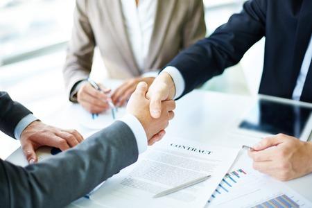 contrato de trabajo: Imagen de socios de negocios apret�n de manos en objetos de negocio en lugar de trabajo Foto de archivo