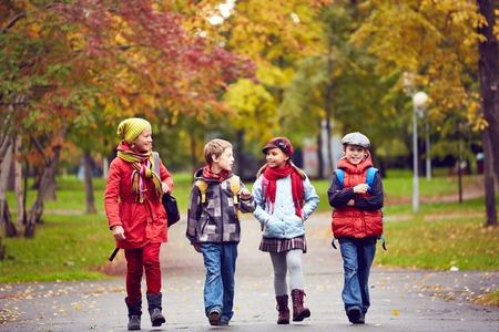 personnes qui marchent: Portrait d'�coliers heureux de parler tout en allant � l'�cole Banque d'images