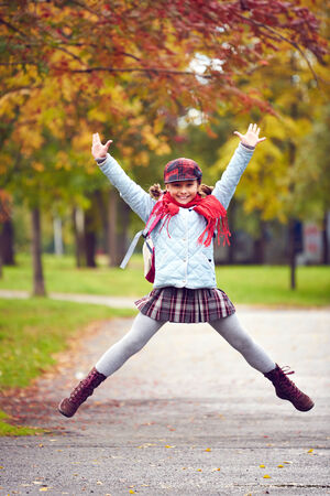Portrait of happy schoolgirl in jump looking at camera photo