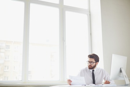 Serious businessman sitting in office and working with papers