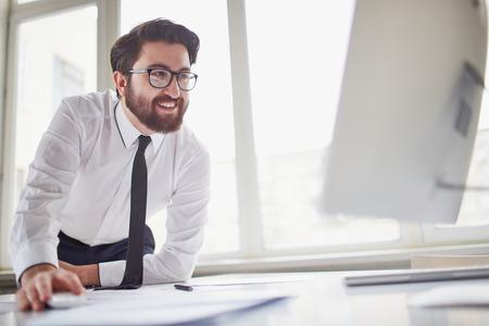 成功した実業家のオフィスにあるコンピューターでの作業